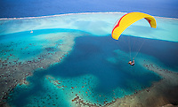Paraglider floats over a beautiful lagoon in Huahine, French Polynesia.  Laminar ocean breeze blows in over the ocean, allowing paragliders to fly for hours and hours on the jungle-clad ridge of Huahine.  Their are only two local pilots on the island and they are only too happy to share their unique spot with us.