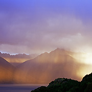 The late sun catches a rain shower on Lake Wakatipu, Queenstown, New Zealand.  Queenstown is nestled on the shores of the crystal clear waters of Lake Wakatipu in the Central Otago region of the South Island of New Zealand. Queenstown is New Zealand's premier tourist destination providing an abundance of year round outdoor activities for both young and old. Queenstown, Central Otago, South Island, New Zealand. Photo Tim Clayton.