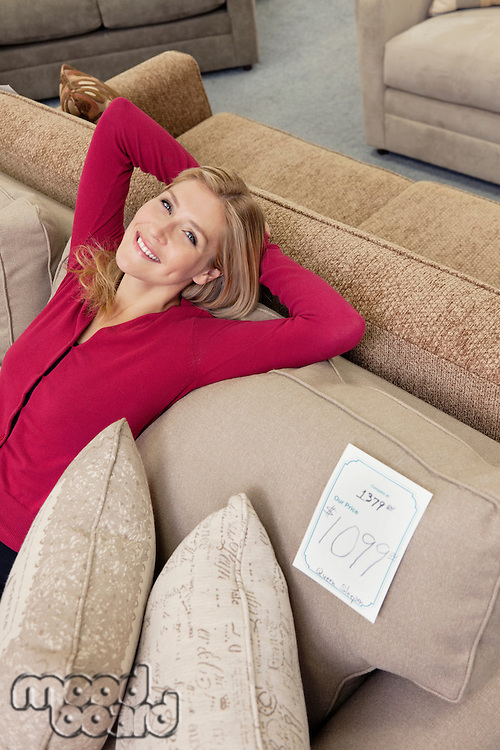 Portrait of a happy young woman with hands behind head relaxing on sofa in furniture store
