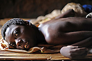 "12-03-27   -- KITGUM, UGANDA --  Bedridden nodding disease victim Vicky Aciro, 14, in her mother's hut near Kitgum, Uganda on Tuesday, March 27.  While the Ugandan Government has opened nodding disease treatment centres at major northern hospitals, many in villages are unable to access the services due to transport costs and the limited mobility of the patient.  Aciro lives across the road from the Okidi Central Village Health Centre and is able to access services, but nurse Agnes Oroma says travelling doctors would be able to assist those living further away.  ""Some can't afford to go to the main hospital and some are stuck in villages which are not near transport. It's really difficult,"" says Oroma.   Photo by Daniel Hayduk"