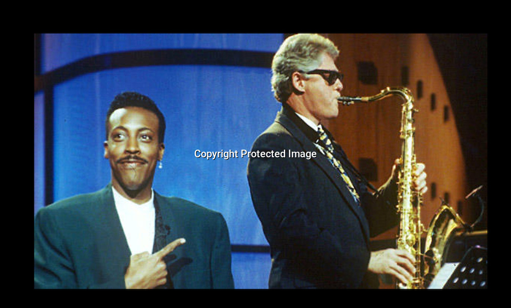 "Gov. Bill Clinton, sitting with the band, turns out an impressive version of ""Heatrbreak Hotel"" as Arsenio Hall gestures approvingly in the musical opening of ""The Arsenio Hall Show"" taping at Paramount Studios in Hollywood, June 3, 1992. (AP Photo/Reed Saxon)"