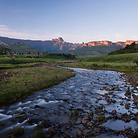 Visit to the Northern Drakensberg Mountains. The iconic Amphitheatre rock formation is located in the Royal Natal National Park and is home to Tugela Falls (the second highest waterfall in the world).