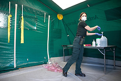 © Licensed to London News Pictures . 21/04/2020. Manchester, UK. Paramedic DONNA PEEL (41 from Trafford) carefully cleans herself and takes off her PPE in a dedicated cleaning tent after delivering a patient with Coronavirus to the Nightingale Hospital . The National Health Service has built a 648 bed field hospital for the treatment of Covid-19 patients , at the historical railway station terminus which now forms the main hall of the Manchester Central Convention Centre . The facility is treating patients from across the North West of England , providing them with general medical care and oxygen therapy after discharge from Intensive Care Units . Photo credit : Joel Goodman/LNP