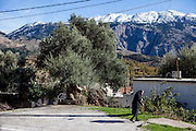 Panagiota (86) who is living with her sister in the small Crete mountain village of Rodovani on the Greek island of Crete. In the back the White Mountains (Lefka Ori).