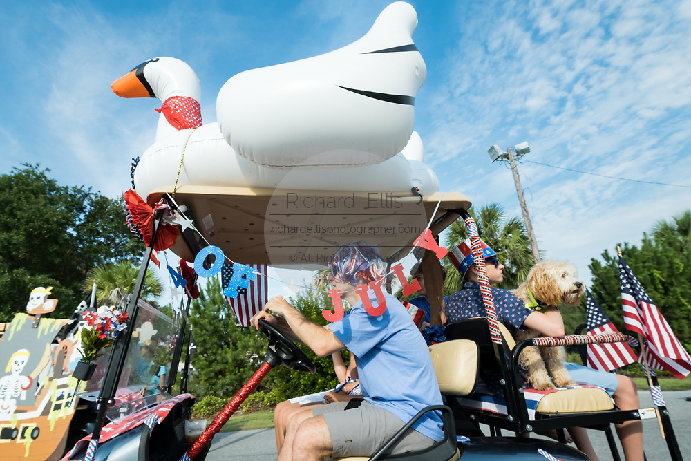 A family drives their decorated golf cart float during the annual Independence Day parade July 4, 2019 in Sullivan's Island, South Carolina. The tiny affluent Sea Island beach community across from Charleston holds an outsized golf cart parade featuring more than 75 decorated carts.