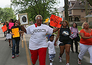 """Lena Ross (center) of Cedar Rapids holds up a picture of her great nephew, Anthony Posley, during a """"Stop the Violence March"""" in Cedar Rapids on Saturday afternoon, May 19, 2012. Posley was murdered in Cedar Rapids in 2006. (Stephen Mally/Freelance)"""