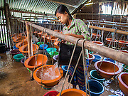 02 NOVEMBER 2014 - TWANTE, YANGON DIVISION, MYANMAR: A worker pours water into bowls in a pottery factory in Twante, Myanmar. The water is used to test the bowl. Twante, about 20 miles from Yangon, is best known for its traditional pottery. The pottery makers are struggling to keep workers in their sheds though. As Myanmar opens up to outside investments and its economy expands, young people are moving to Yangon to take jobs in the better paying tourist industry or in the factories that are springing up around Yangon.    PHOTO BY JACK KURTZ
