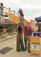 Brooklyn, New York, USA. 10th August 2013. Stilt walker KAE BURKE, of Lady Circus, and BOB YORBURG, AKA Professor Phineas Feelgood, The World's Greatest Magician in the World, entertain visitors at the 3rd Annual Coney Island History Day celebration.