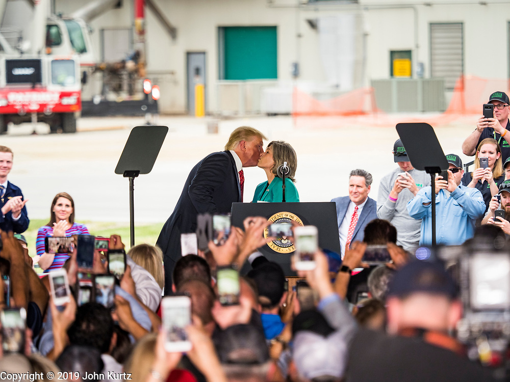 11 JUNE 2019 - COUNCIL BLUFFS, IOWA: U.S. President DONALD J. TRUMP, left, kisses U.S. Senator JONI ERNST on the cheek when he took the podium to speak at Southwest Iowa Renewable Energy. President Trump visited Southwest Iowa Renewable Energy in Council Bluffs Tuesday to announce that his administration was relaxing rules on E15, an ethanol additive for gasoline. Iowa is one of the leading ethanol producers in the U.S. and Iowa corn farmers hope the administration's change in E15 rules will spur demand for corn.          PHOTO BY JACK KURTZ