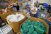 Apr. 3, 2009 -- MESA, AZ: YOSKO HARBER, left, and LAURA QUIGLEY, and other volunteers at the United Food Bank, fill shopping carts for clients. A spokesperson for the United Food Bank in Mesa, AZ, said demand has increased by more than 100 percent in the last year. She said that at this time in 2008, about 175 people a week (the food bank is open one day a week) bought 200 boxes a food but now they were seeing about 350 people per week and they were buying 400-450 boxes of food per week. Each box of food cost $16 and contains enough food for five meals for two people, including meat, fruit and vegetables and starches. In addition to the food boxes, the food bank gives away perishables, like fresh baked goods and produce, that are donated by Phoenix area grocery stores and food producers. She said the number of donations to the food bank have increased as the economy has worsened but each donation is smaller and the gap between donations and what the food bank needs is widening.    Photo by Jack Kurtz / ZUMA Press