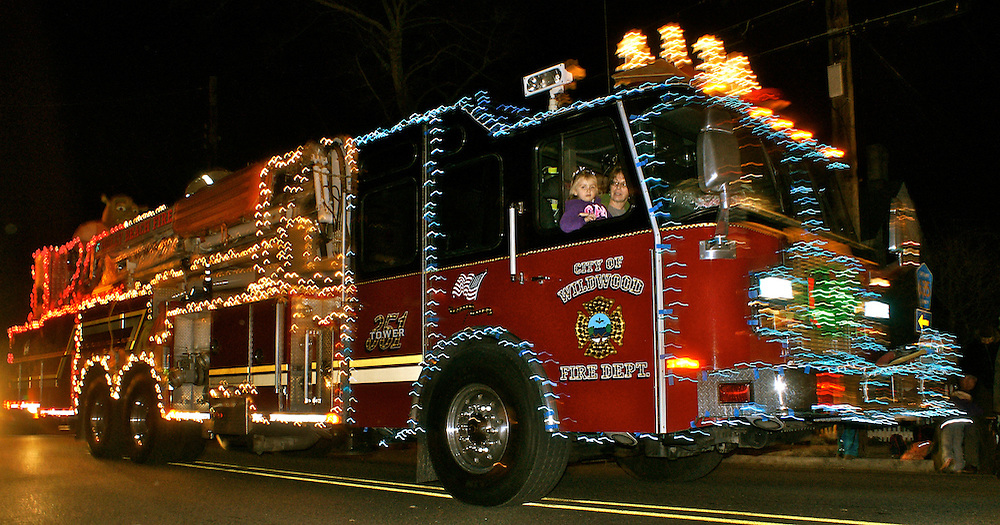 Six year old girl and mother ride in fire engine with holiday lights in Cape May Christmas parade
