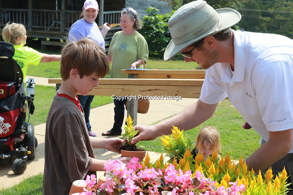 LIBBY EZELL | BUY AT PHOTOS.DJOURNAL.COM<br /> Landon Heaton, left, helps Graham Hartley, 9 with putting a plant into a pot Saturday at the Arc in the Park event