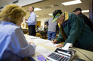 Hertz Real Estate Services executive assistant Denise Vallandingham (from left) watches as Gaylord Jones of Eagle Grove, Iowa registers before the start of a farm auction at the Eagle Grove Masonic Lodge in Eagle Grove, Iowa on Thursday, October 18, 2012. Jones purchased the eighty acre property for $848,000 at $10,600 per acre.
