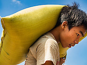 22 OCTOBER 2015 - YANGON, MYANMAR: Stevedores carry sacks of rice which weigh more than 100 pounds each to shore from barges that bring the rice into Yangon from farms in the countryside.    PHOTO BY JACK KURTZ