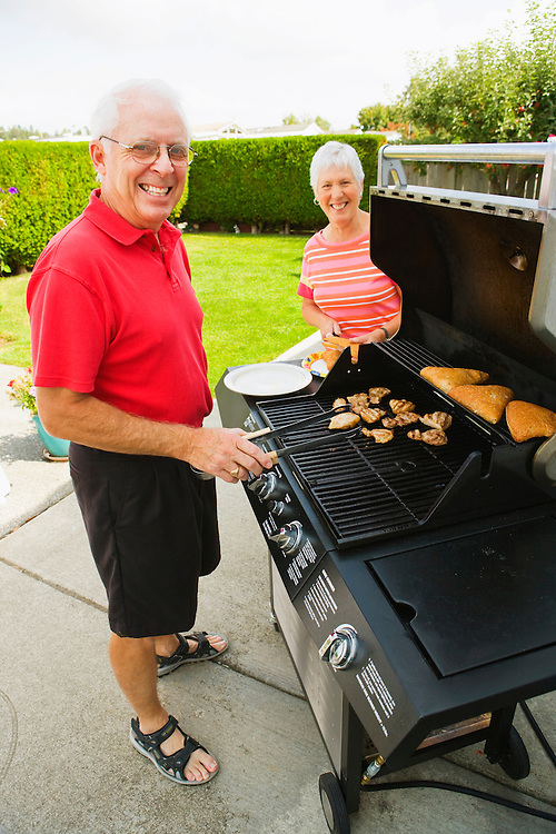 Portrait of a mature couple cooking at a barbeque on their patio
