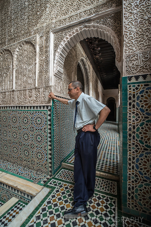 An employee stands inside Madrasa Bou Inania a koranic school in Fes, Morocco. Founded in 1351–56 this is widely acknowledged as an excellent example of Marinid architecture. The madrasa is one of the few religious places in Morocco that is accessible for non-Islamic visitors.