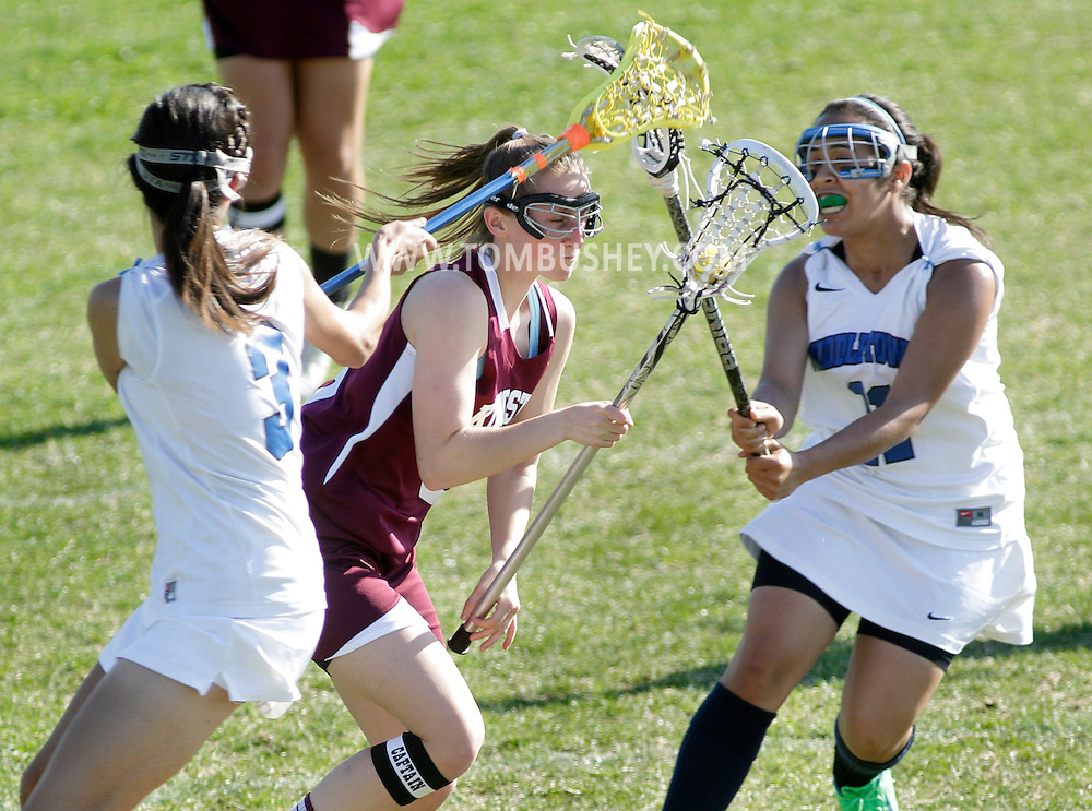 Kingston's Joey Lynn Henderson carries the ball between Middletown's Cindy Fierro, left, and Bethany Hernandez during a game in Middletown on Thursday, May 2, 2013.