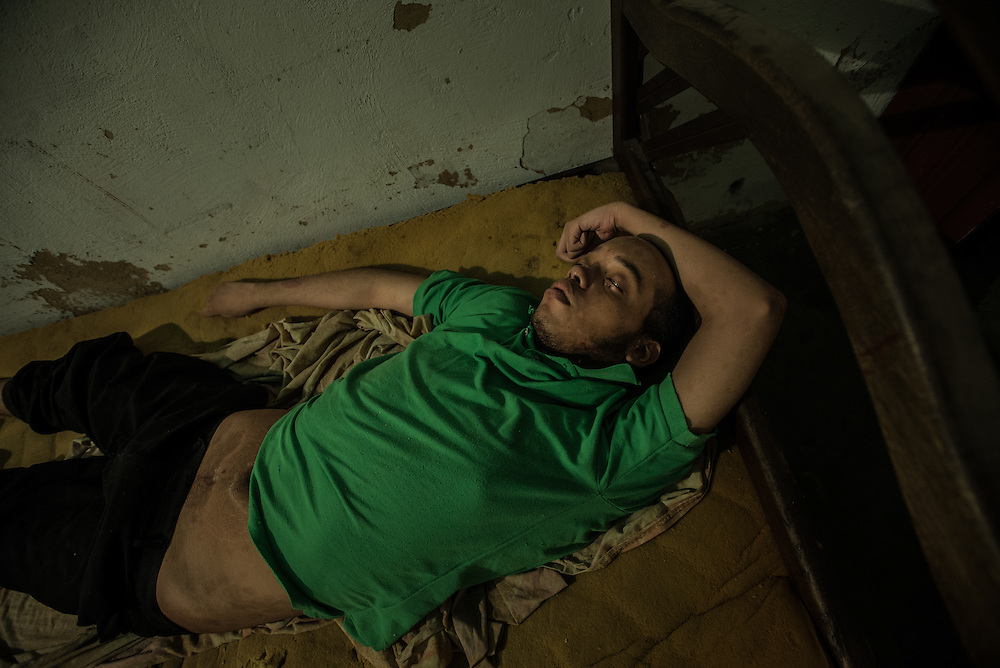 "MARACAY, VENEZUELA - JULY 4, 2016: Schizophrenic Gerardo Simeone sleeps on a mattress in his bedroom in the middle of the day.  He spends most of his days either sleeping, or standing in a corner in silence in his family's living room, rarely even making eye contact with members of his family.  His parents remember how he used to be when he was younger…before he became ill - recalling how affectionate and talkative he was. ""He was so kind and loving,"" said his mother, Evelin.  Gerardo's brother Accel is also schizophrenic. Their parents spend hours each week searching pharmacies for the psychiatric drugs that thier sons need, which are very difficult to find, because of nationwide shortages.  ""I am tired,"" Evelin said. ""This is too much sometimes"".  PHOTO: Meridith Kohut for The New York Times"