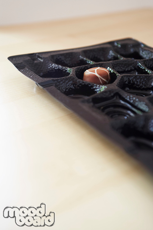 Chocolate box with only one truffle remaining close-up