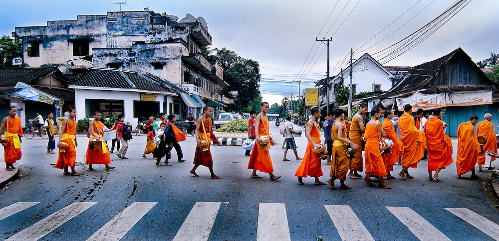 Buddhist monks walking the streets of Luang Prabang early in the morning collecting alms.