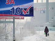Billboard of Vladimir Putins United Russia party for the Duma elections and a woman carrying water and her shopping from a marketplace home. Yakutsk is a city in the Russian Far East, located about 4 degrees (450 km) below the Arctic Circle. It is the capital of the Sakha (Yakutia) Republic (formerly the Yakut Autonomous Soviet Socialist Republic), Russia and a major port on the Lena River. Yakutsk is one of the coldest cities on earth, with winter temperatures averaging -40.9 degrees Celsius.