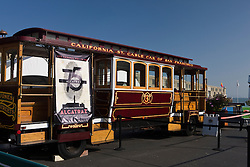 A California Street Cable Car of San Francisco is parked at Pier 33, where tourists board ferries to Alcatraz Island, Golden Gate National Recreation Area, San Francisco, California.