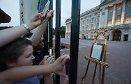 UNITED KINGDOM, London : A photo showing crowds outside Buckingham Palace after an easel stands in the forecourt announcing the birth of a baby boyat 4.24pm to Prince William and Catherine, Duchess of Cambridge, at St Mary's Hospital in London on July 22, 2013.  Prince William's wife Kate on Monday gave birth to a baby boy who will one day be heir to the British throne, Kensington Palace said in a statement.