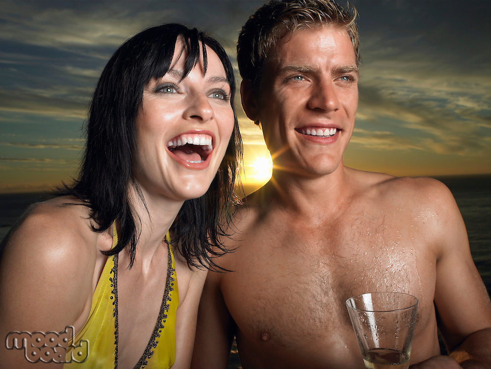 Man and woman in bathing suits laughing sunset outdoors