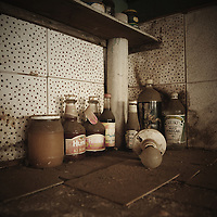 Old dusty jars and bottles in kitchen with spotty wall tiles and filthy work top