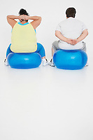 Overweight man and woman Exercising on exercise Balls back view