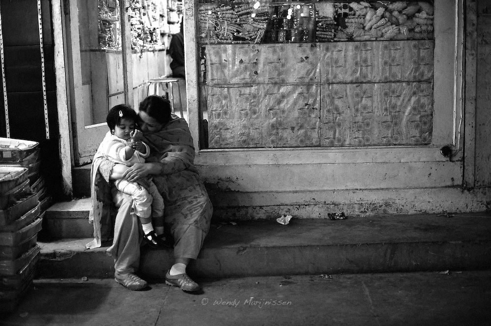 A grandmother is playing with her grandchild outside an accessories shop at Liberty market. Lahore, Pakistan, 2009