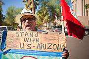 17 OCTOBER 2011 - PHOENIX, AZ:  TOMAS ALEJO, a pro-immigration protester, tries to shout at Republican Presidential candidate Michele Bachmann as she the leaves the Arizona State Capitol in Phoenix, Monday. Bachmann met with Republican Arizona legislators and Republican members of the state's Congressional delegation Monday morning to talk about illegal immigration and border security. During the meeting she pledged that if she were elected US President, she would construct a fence along the US - Mexico border.   PHOTO BY JACK KURTZ