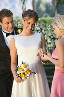 Bride showing ring to bridesmaid, groom looking on