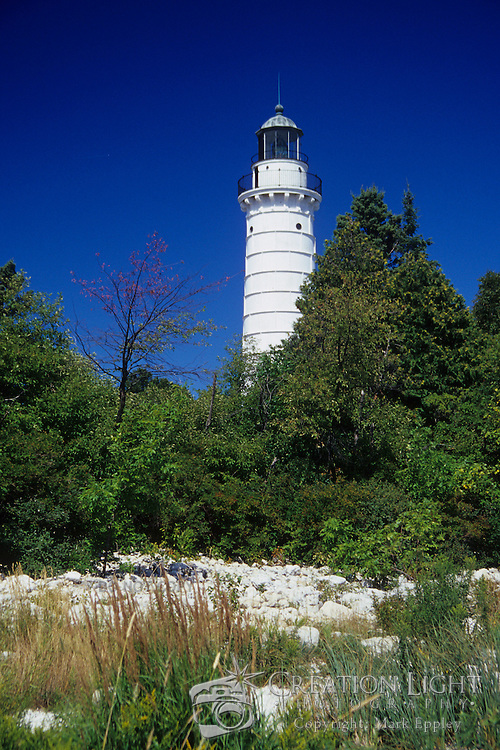 The Cana Island lighthouse 89 feet tall and is visible for 18 miles.  It is located just north of Baileys Harbor in Door County, Wisconsin...Door County on the Door Peninsula in Wisconsin is a popular vacation location in the Midwest.  The Peninsula is south of the Upper Peninsula of Michigan.  It offers a great place to relax and enjoy nature. Door County has five state parks, ten lighthouses, and beautiful sandy beaches with the fresh, clear water of Lake Michigan.