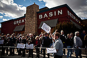 A volunteer hands out signs to supporters lined up early to see GOP presidential candidate Newt Gingrich at a campaign event at Great Basin Brewing Company in Reno, Nevada, February 1, 2012.