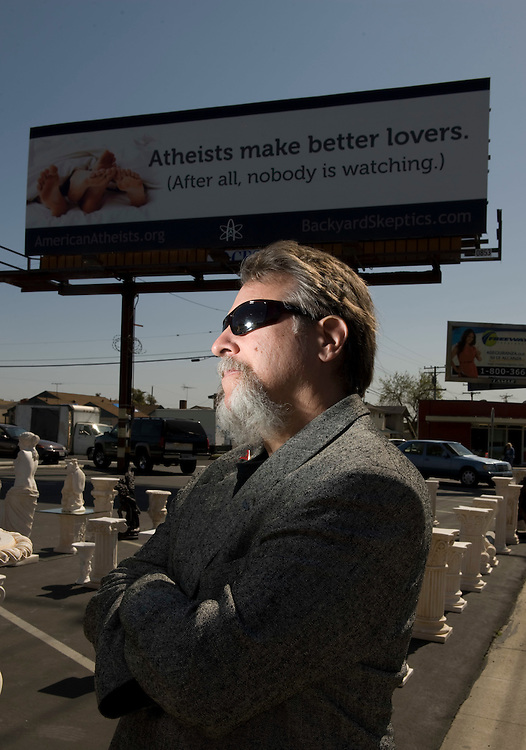 """Bruce Gleason, the """"most outted atheist"""" in Orange County, and leader of Back Yard Skeptics, poses with the Valentine's day billboard the group put up along Beach Blvd in Midway City."""
