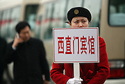 A woman holds a sign to guide delegates  from China's parliament back to thier hotels from the Great Hall of the People in Beijing. China will boost its 2007 defense budget by the most in five years, as an expanding economy gives the world's largest regular army the means to upgrade its equipment to rival Taiwan, Japan and the U.S.