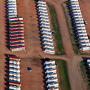 "A man camp outside of Watford City, North Dakota.  Theoil boom has brought unprecedented prosperity to little towns like Watford City, N.D. (population 1,744), it has also exacerbated problems in housing, infrastructure and traffic...Williston (""Kuwait on the Prairie""), Watford City and their neighboring towns in North Dakota sit atop the biggest lake of oil to be discovered in North America since Alaska's Prudhoe Bay in 1968. ..There are too many unfilled jobs and not enough empty beds to accommodate the masses of people looking for work in the oil boom, man camps have sprung up throughout the formerly idyllic  prairie. They are dormitory-style buildings, FEMA trailers, or RV's, and a temporary solution to housing workers but are straining utilities and stretching towns emergency services."