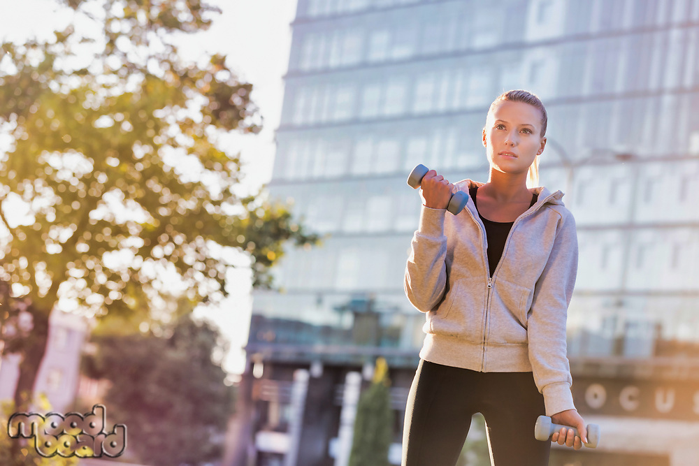 Young attractive woman exercising and holding dumbell