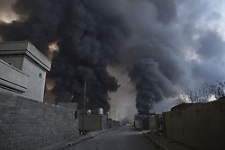 October 21, 2016 - Qayyarah, Iraqi-Kurdistan, Iraq - A cloud of smoke, rising from burning oil wells that have been alight for around two months, is seen towering over houses in the town of Qayyarah, Iraq. The oil wells, located in a neighbourhood on the edge of the town, were set alight in July by retreating Islamic State militants as part of a scorched earth policy...Since being retaken from the Islamic State the town of Qayyarah has become an important staging post for the Iraqi Army, and some US support elements, in the buildup to the Mosul offensive. (Credit Image: © Matt Cetti-Roberts/London News Pictures via ZUMA Wire)