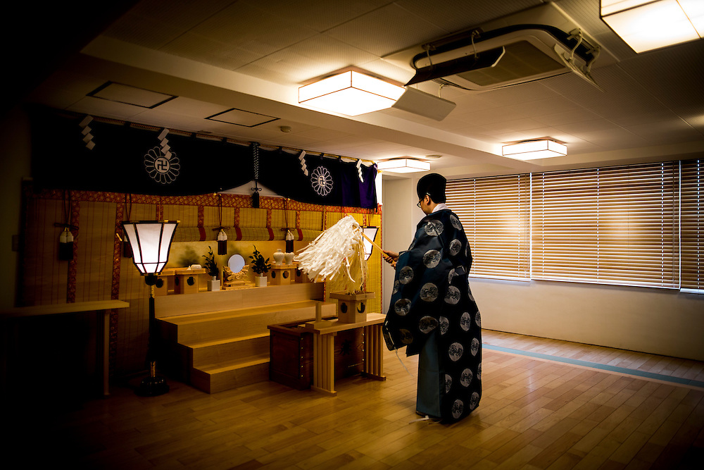 """TOKYO, JAPAN - JUNE 27 :  A shinto priest staging a prayer to a deceased anime figure in front of an altar in Akihabara shrine in Akihabara, Tokyo, Japan on June 27, 2016. A newly opened Akihabara Shrine offers a memorial services for """"deceased"""" anime figures. Photo by Richard Atrero de Guzman"""