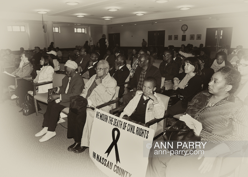"""May 9, 2011 - MINEOLA, NY:  Amid adults at public hearing, young Ramel Smith, Jr., sitting with sign: """"We Mourn the Death of Civil Rights in Nassau County."""" Front row, fourth from right, is Golena White of Hempstead. Nassau County Legislature's public hearing on Legislative Redistricting, at Nassau County Executive and Legislative Building, 1550 Franklin Avenue, Mineola, Long Island, New York, USA."""
