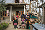 Abdul Ahad Ganai and his family stand in front of their collapsed house in Narbal village, Jammu and Kashmir, India, on 24th March 2015. When the floods hit in the middle of the night, Abdul Ahad Ganai and his family with 5 children was lucky to escape with their lives despite half of his family home collapsing. Save the Children supported the family with emergency shelter kits, blankets, hygiene items, education kits and food baskets. Photo by Suzanne Lee for Save the Children