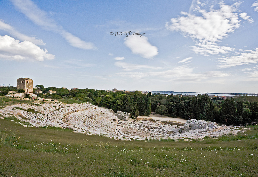 Sicily, Syracuse, Greek theater, 5th century, view of the theater from the hill above showing how the entire auditorium fits into the slope of the hill.  Landscape and ocean sea in the distance, blue sy and white clouds above.