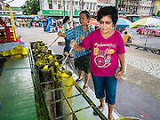 20 JULY 2015 - NONTHABURI, NONTHABURI, THAILAND:  A woman puts wax into a candle mold for the Rains Retreat (also called Buddhist Lent) on Nonthaburi Pier, the end of the Chao Phraya Express Boat line in Nonthaburi, a suburb of Bangkok. This is the north end of a plan to develop the Chao Phraya River riverfront. The Chao Phraya promenade is development project of parks, walkways and recreational areas on the Chao Phraya River between Pin Klao and Phra Nang Klao Bridges. The 14 kilometer long promenade will cost approximately 14 billion Baht (407 million US Dollars). The project involves the forced eviction of more than 200 communities of people who live along the river, a dozen riverfront  temples, several schools, and privately-owned piers on both sides of the Chao Phraya River. Construction is scheduled on the project is scheduled to start in early 2016. There has been very little public input on the planned redevelopment.          PHOTO BY JACK KURTZ