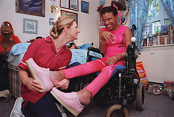 Care manager in residential care centre helping young woman with Cerebral Palsy to put her shoes on,