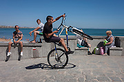 A youth on bike performs wheelies on the seafront of Cascais, near Lisbon, Portugal.