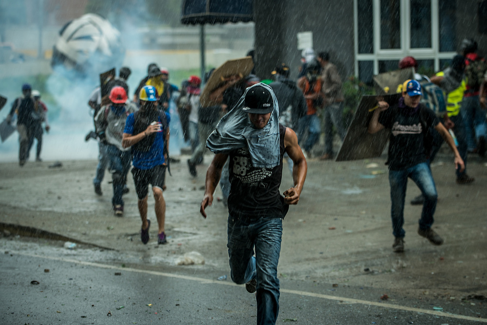 CARACAS, VENEZUELA - MAY 24, 2017:  Anti-government protesters run in the rain while being chased by security forces, who  were heavily tear gassing and firing rubber bullets and buckshot at them.  The streets of Caracas and other cities across Venezuela have been filled with tens of thousands of demonstrators for nearly 100 days of massive protests, held since April 1st. Protesters are enraged at the government for becoming an increasingly repressive, authoritarian regime that has delayed elections, used armed government loyalist to threaten dissidents, called for the Constitution to be re-written to favor them, jailed and tortured protesters and members of the political opposition, and whose corruption and failed economic policy has caused the current economic crisis that has led to widespread food and medicine shortages across the country.  Independent local media report nearly 100 people have been killed during protests and protest-related riots and looting.  The government currently only officially reports 75 deaths.  Over 2,000 people have been injured, and over 3,000 protesters have been detained by authorities.  PHOTO: Meridith Kohut