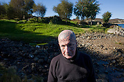 In cold winter sunshine, a portrait of tattoed hermit  Tom Leppard outside his secret hideaway shelter on Skye