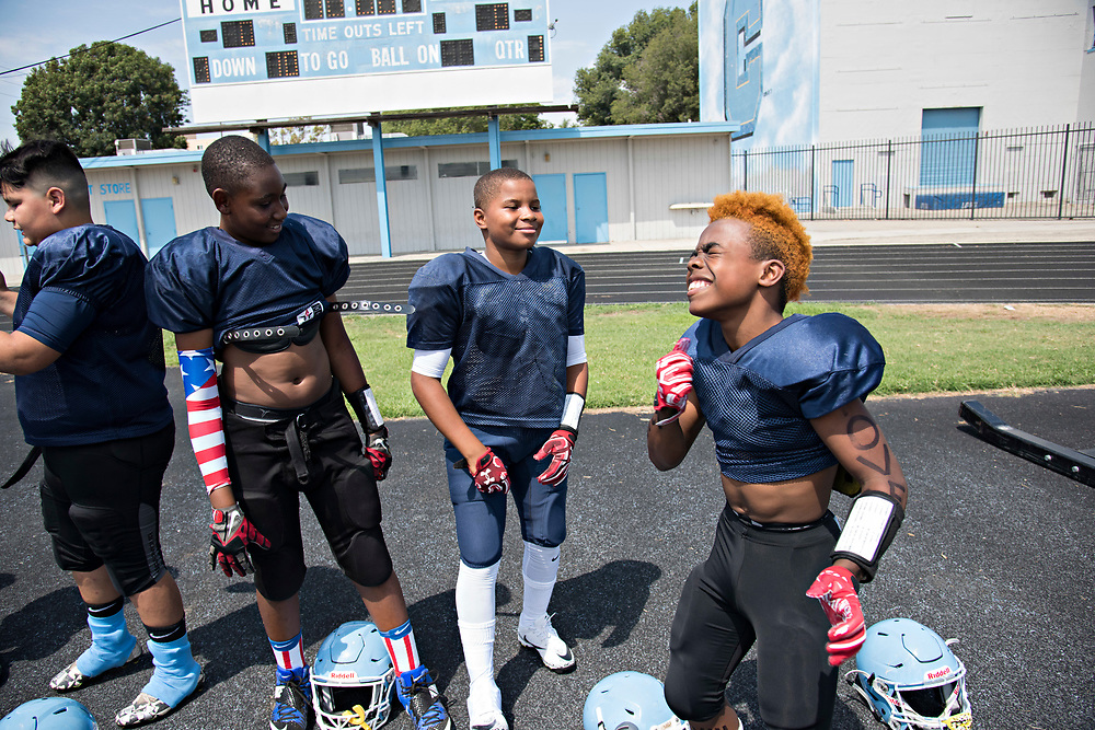 "While waiting to have their equipment checked before the game, Maxwell ""Bunchie"" Young, 10, right, and his Hub City TarHeels teammates joke around, practicing their end zone dances."